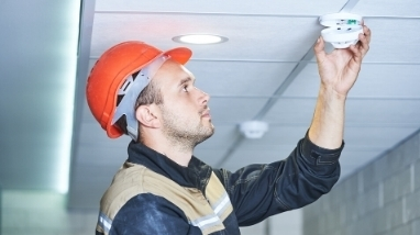 worker checking smoke alarms for fire safety
