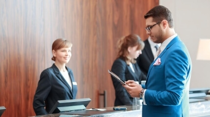 business man filling out check in form at hotel front desk
